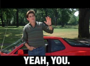 Sixteen Candles movie still - Jake Ryan character in front of red Ferrari waving 'Yeah You'